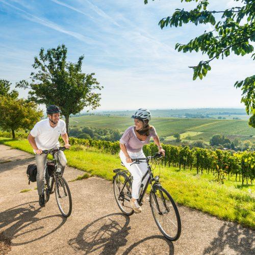 Ein Mann und eine Frau fahren mit dem Fahrrad über einen Weg durch einen Weinberg