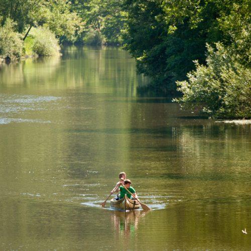 Zwei Männer paddeln in einem Kanu auf einem Fluss
