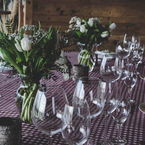 Gedeckter Tisch mit Weingläsern und weißen Blumensträußen