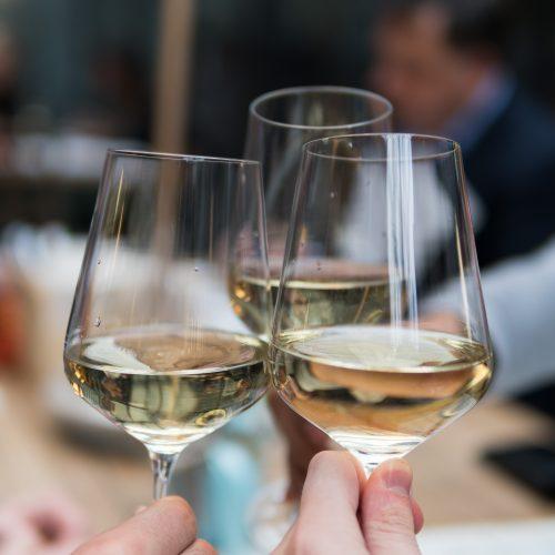 Ausschnitt von drei Gläsern, mit Weißwein gefüllt, mit denen angestoßen wird
